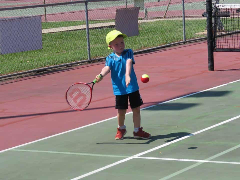 young boy playing tennis
